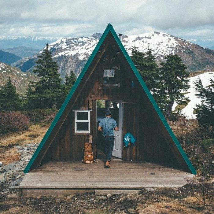 Hütte-Dreieck-Gebirge-Schnee-Nadelbäume-Mann