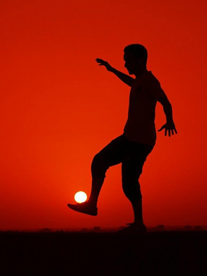 Mann-Fußballer-Sonne-Ball-Sonnenuntergang