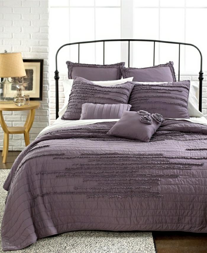 Schlafzimmer-Fenster-weiße-Ziegelwände-hölzerner-Nachttisch-Lampe-Bett-Schmiedeeisen-Bettwäsche-lila
