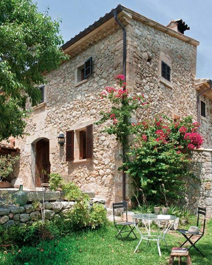 Steinhaus-Villa-mediterraner-Stil-Garten-Grün-rosige-Blumen-Stühle-Schmiedeeisen