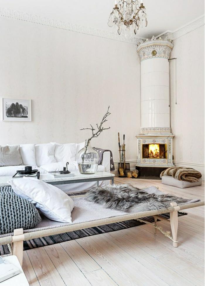 Wohnzimmer-skandinavisch-weiß-Kamin-Sofa-Brennhölzer-Schlafdecken-Kronleuchter