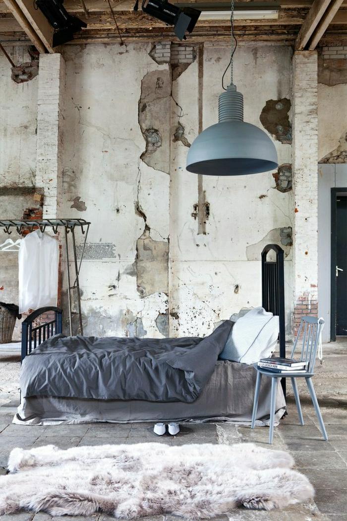 alte-Wohnung-Ziegelwände-industrielle-Lampe-Tierhaut-blauer-Stuhl-lila-Bettwäsche