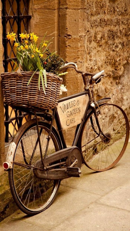altes-Fahrrad-retro-Korb-gelbe-Blumen-Steingebäude