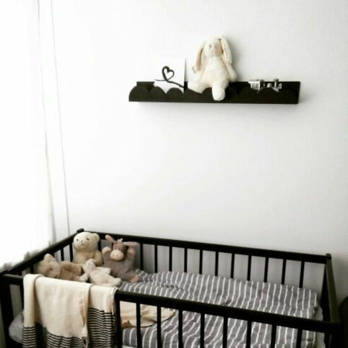 babyzimmer-design-schwarzes-regal-an-der-weißen-wand-über-dem-babybett