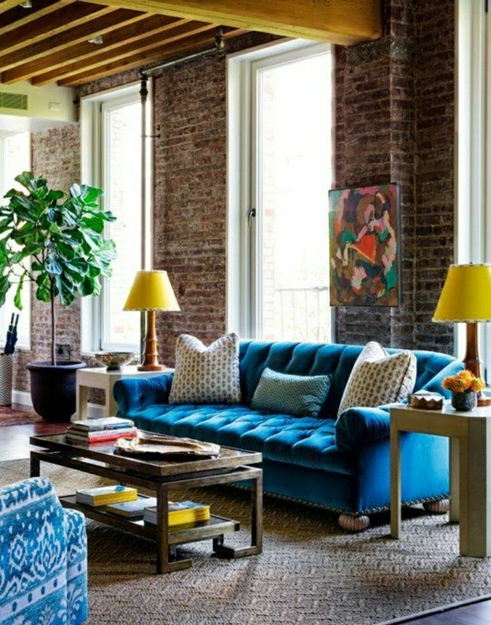 blaues-Samt-Chesterfield-Sofa-gelbe-Lampen-Pflanzen