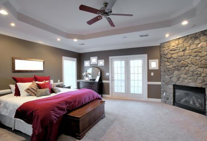 deckenbeleuchtung-für-schlafzimmer-stein-wände-bett-mit-roten-bettwäschen