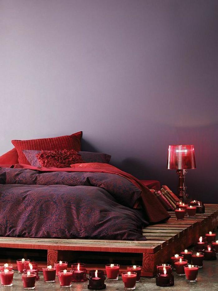 exotisches-Schlafzimmer-lila-Wände-Bettwäsche-rot-lila-Ornamente-Kissen-Palettenbett-rote-Lampe-Kerzen