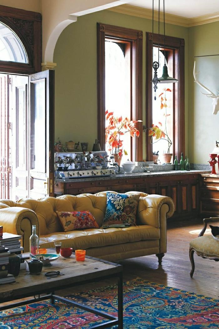 gelbes-Chesterfield-Sofa-Kissen-Boho-Chic-Stil-bunter-Teppich-Kaffeemaschine-Blumentöpfe