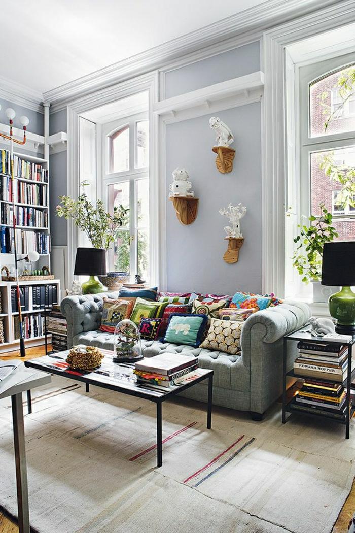 helles-Wohnzimmer-Bücherwand-graue-Wände-Figuren-an-der-Wand-Chesterfield-bunte-Kissen