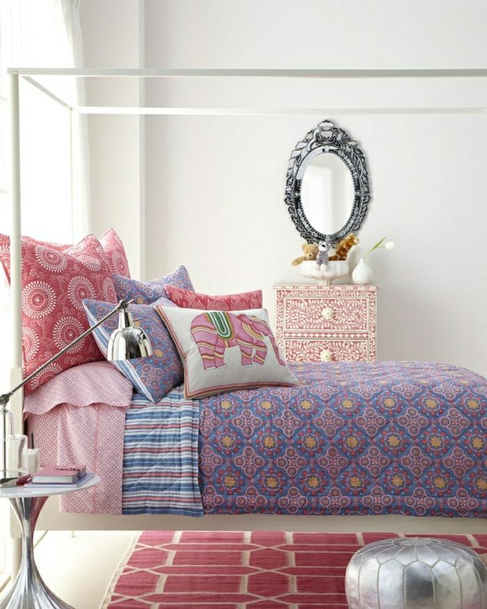 lila-Bettwäsche-indische-Motiven-rosa-Kissen-Kommode-Spiegel-Vase-weiße-Tulpe-Metalllampe-graphischer-Teppich