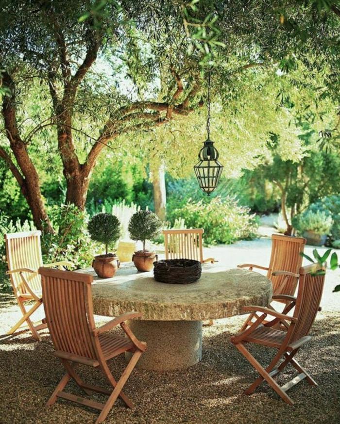 mediterrane-Gartengestaltung-Steintisch-hölzerne-Stühle-Laterne