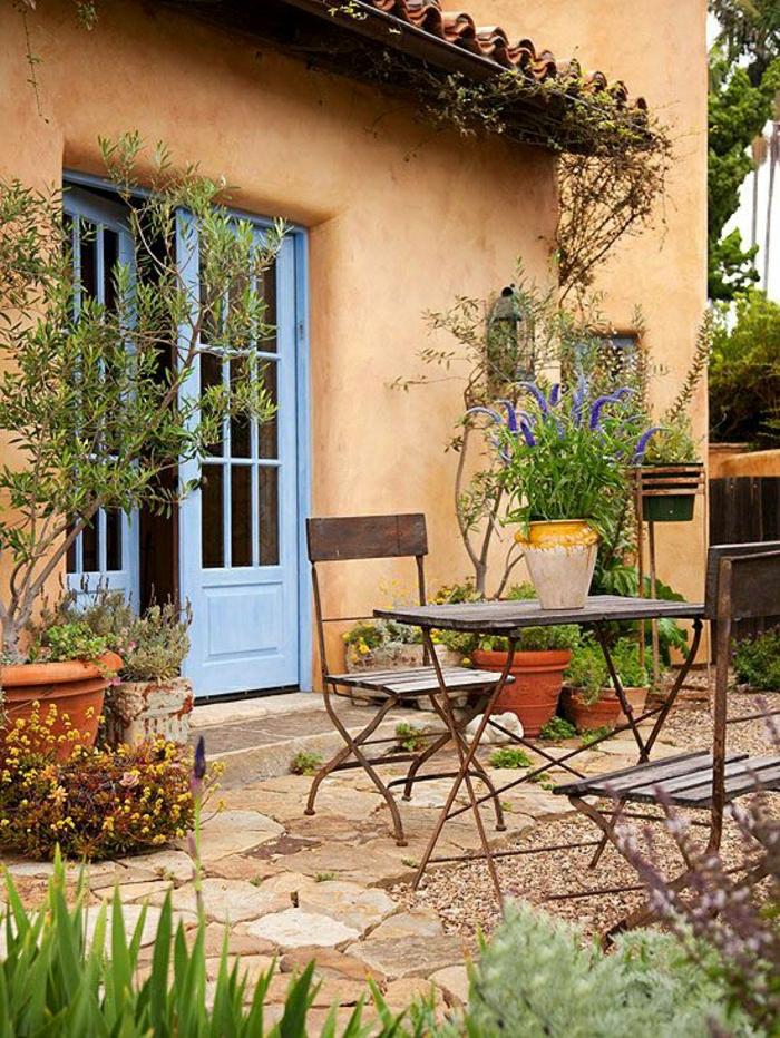 mediterrane-Gartengestaltung-Tisch-Stühle-Schmiedeeisen-Blumentopf-blaue-Tür