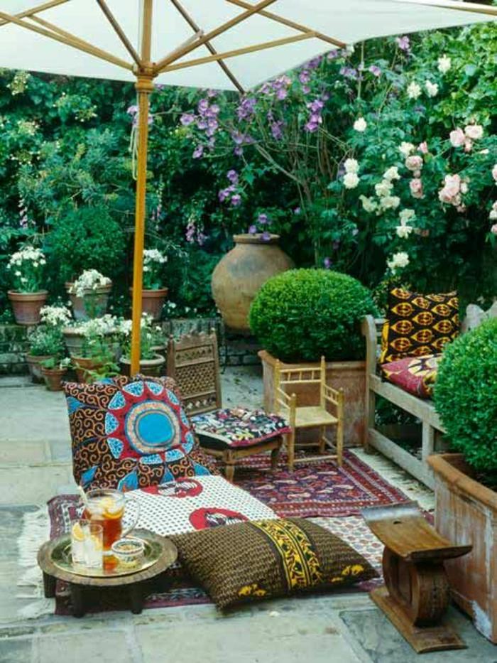 mediterraner-Garten-Sonnenschirm-Getränke-Blumen-bunte-Kissen