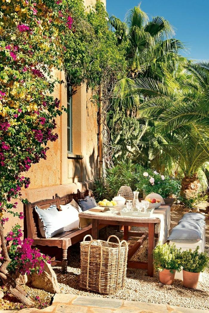 mediterraner-Garten-altes-Haus-hölzerne-Möbel-Früchte-Gläser-Rattankorb-Blumentöpfe-Palmen-dekorative-Steine