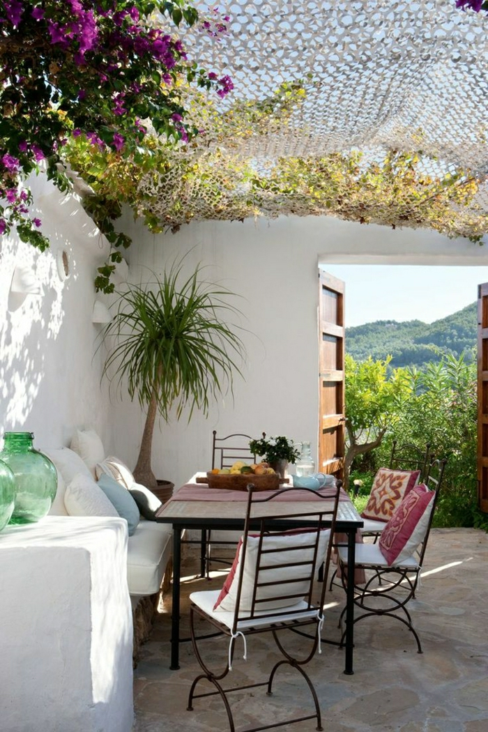 mediterraner-Garten-lila-Blumen-Palmen-bunte-Kissen-Schmiedeeisen-Früchte