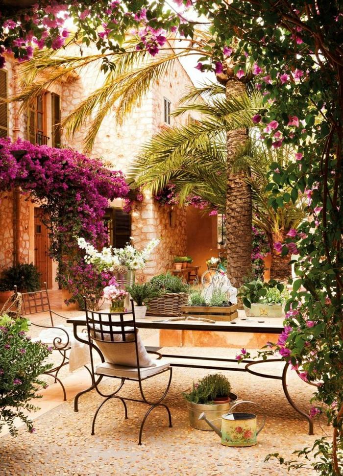 mediterraner-Garten-rosige-Blumen-Stühle-Tisch-Schmiedeeisen-Palmen-Blumentöpfe-Gießkanne