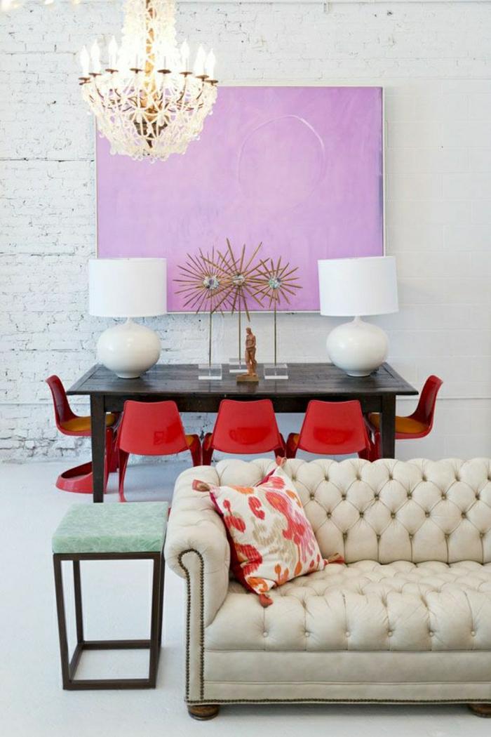 modernes-Interieur-beige-Chesterfield-Esstisch-rote-Plastikstühle-lila-Bild