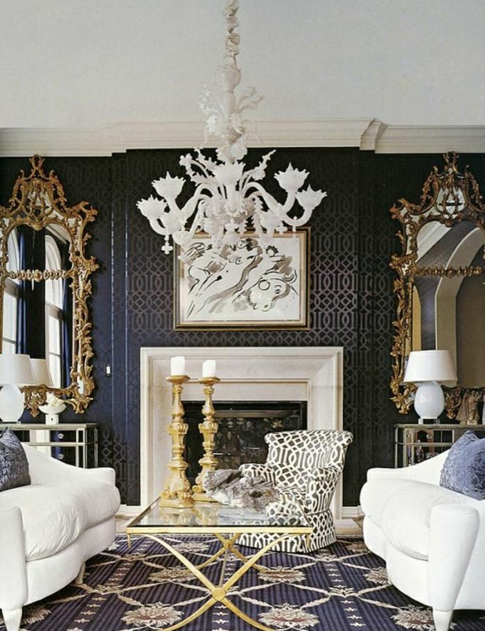 reich-dekoriertes-Barock-Wohnzimmer-Kronleuchter-graphischer-Sessel-Spiegel-goldene-Elemente-weiße-Sofas-Kamin-massive-Kerzenhalter