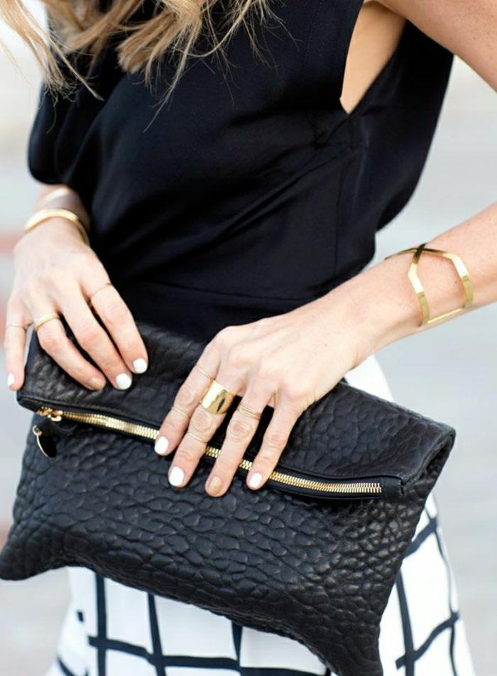 schwarze-Clutch-goldener-Schmuck-Ringe-Armbänder-schwarzer-Top-Rock-graphisches-Muster
