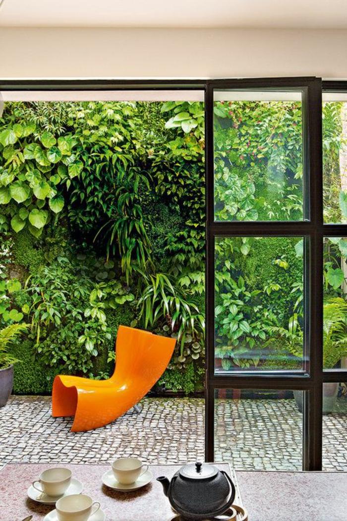 terrassenboden-aus-stein-orange-stuhl-gläserne-wände