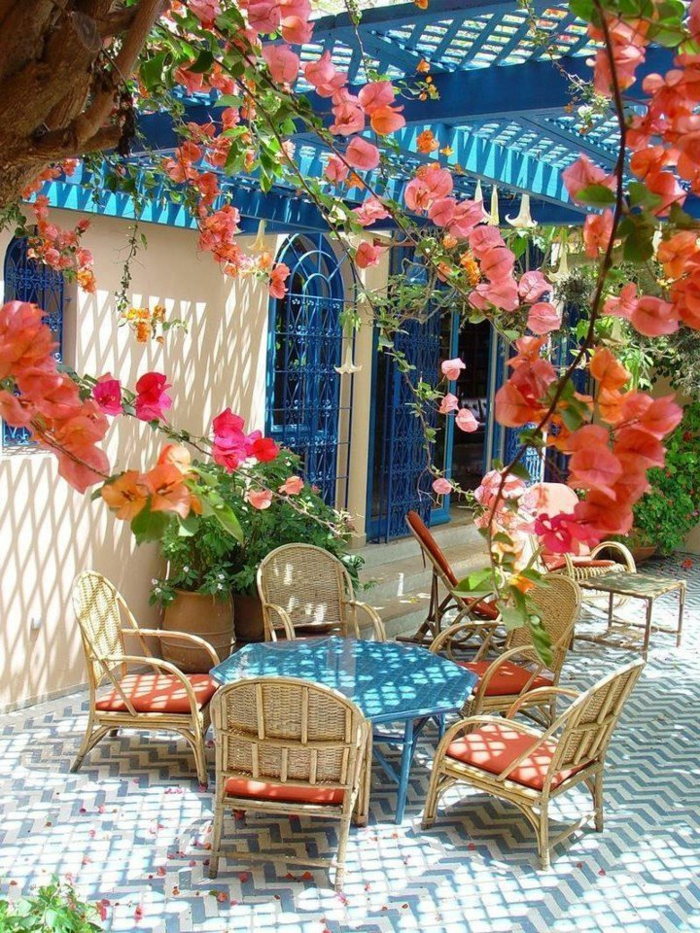 terrassenboden-aus-stein-rote-süße-blümchen-tisch-und-stühle