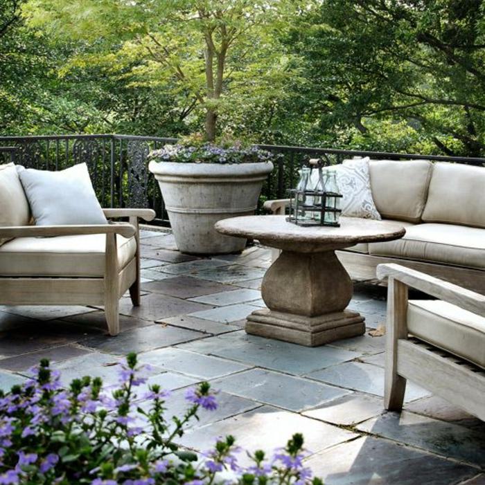 terrassenboden-aus-stein-runder-kaffeetisch-und-moderne-sofas
