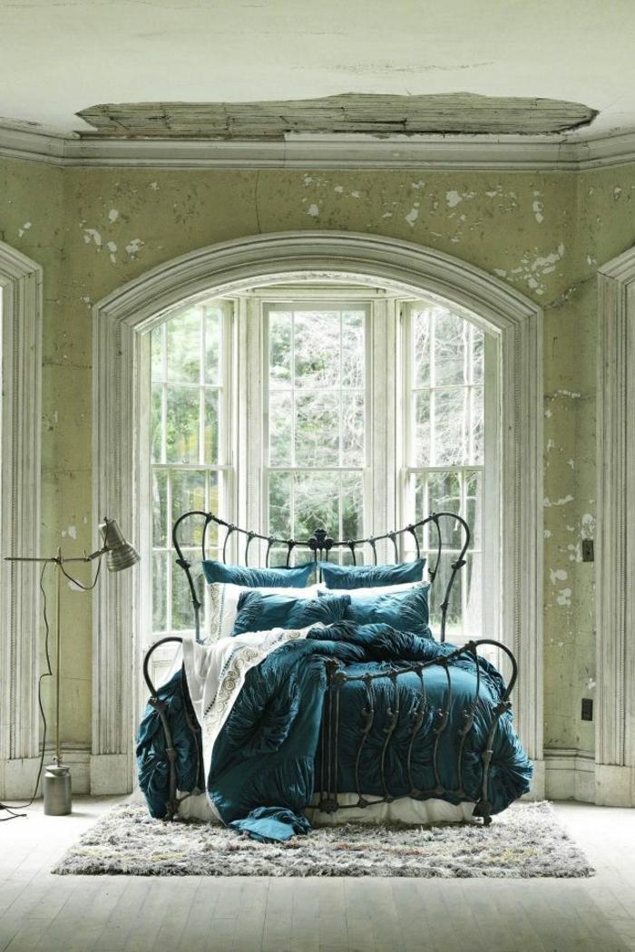 vintage-Schlafzimmer-altes-Haus-große-Fenster-flaumiger-Teppich-Bett-Schmiedeeisen-schöne-türkisblaue-Bettwäsche