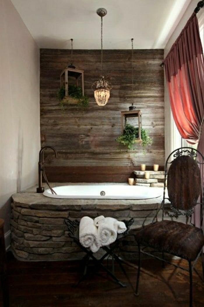 Badezimmer-rustikales-Design-Badewanne-massive-Steine-hölzerne-Wand-Kerzen-rote-Gardinen-aristokratischer-Stuhl