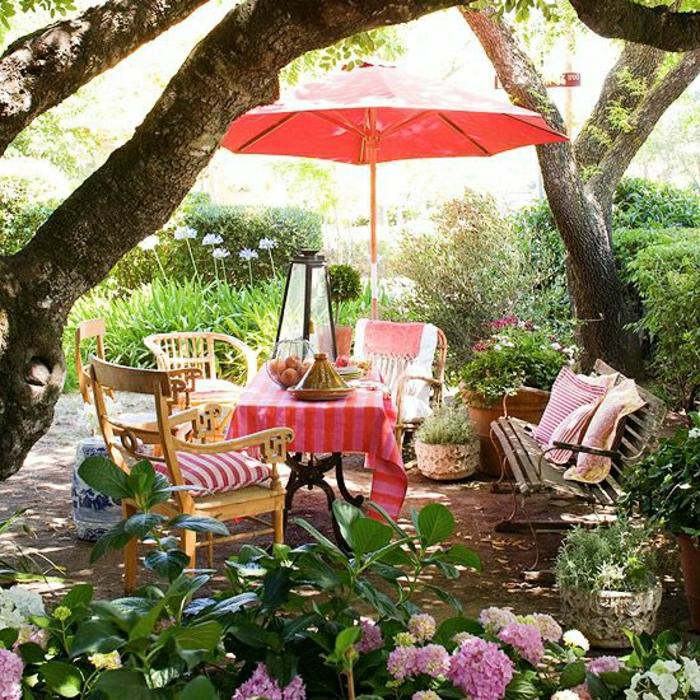 Garten-grell-rosiger-Schirm-rosige-Tischdecke-Bank-Blumen
