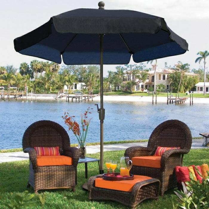 Gartenschirm-schwarz-stilvoll-Rattan-Möbel-orange-Kissen-Gras-Meer
