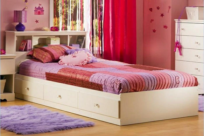 Kinderzimmer-rosige-Wände-flaumiger-Teppich-weißes-Bett-Schubladen-Bettwäsche-lila-rot-rosa-Kissen-Kommode-Spielzeuge