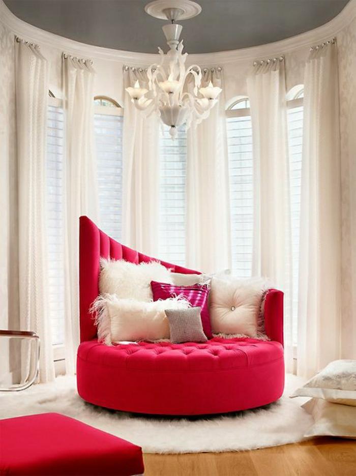 Luxus-Gestaltung-roter-Sessel-schick-Kissen-flaumiger-Teppich-weiße-Gardinen-Kronleuchter-extravagant