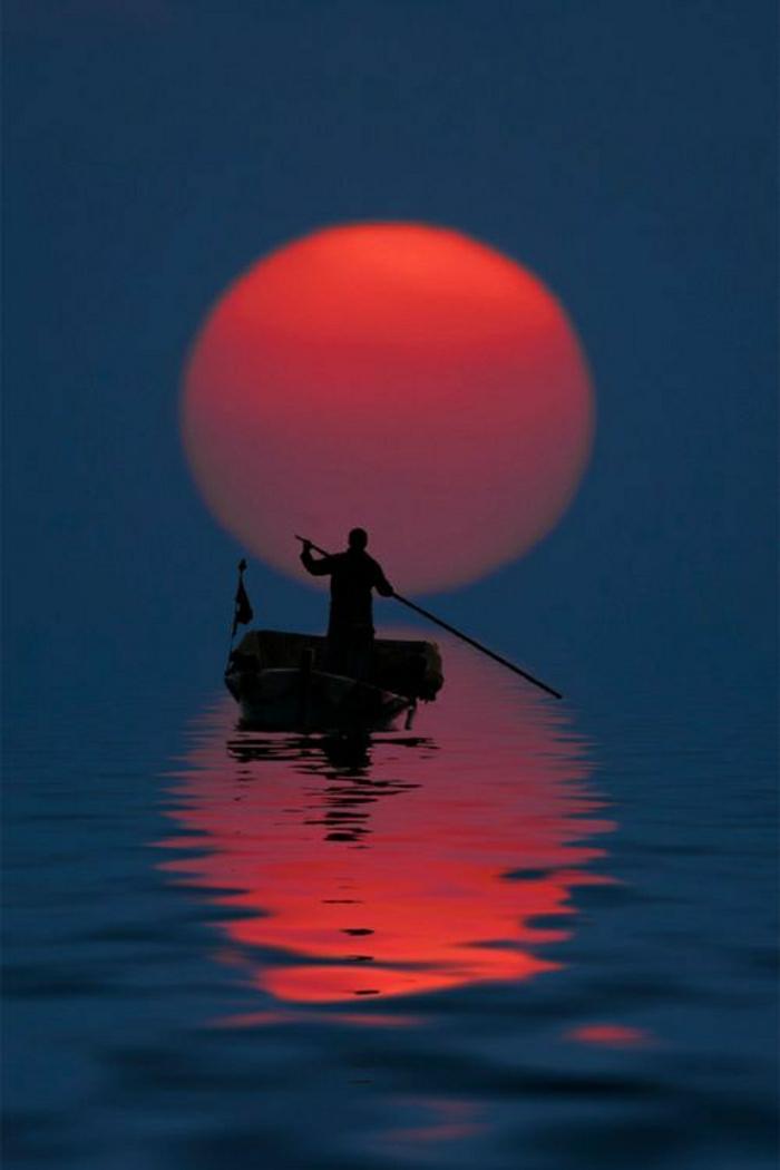 Mann-Boot-Sonnenuntergang-Wasser-Spiegelung
