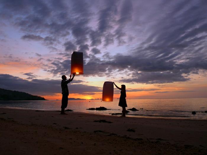 Mann-Frau-Strand-Sonnenuntergang-fliegende-Laternen