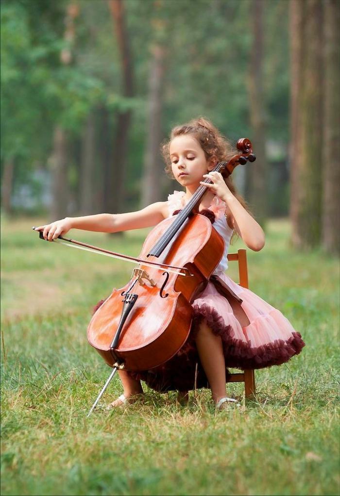 Natur-Gras-kleines-Mädchen-Cello-spielend