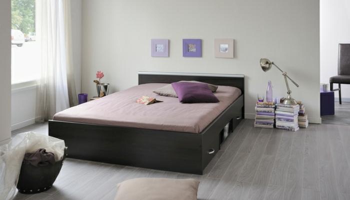 Schlafzimmer-breites-Bett-Schubladen-lila-Bettwäsche-Kissen-Bilder-Rahmen-lila-Nuancen-Bücher-Flasche-Glas-stilvoll