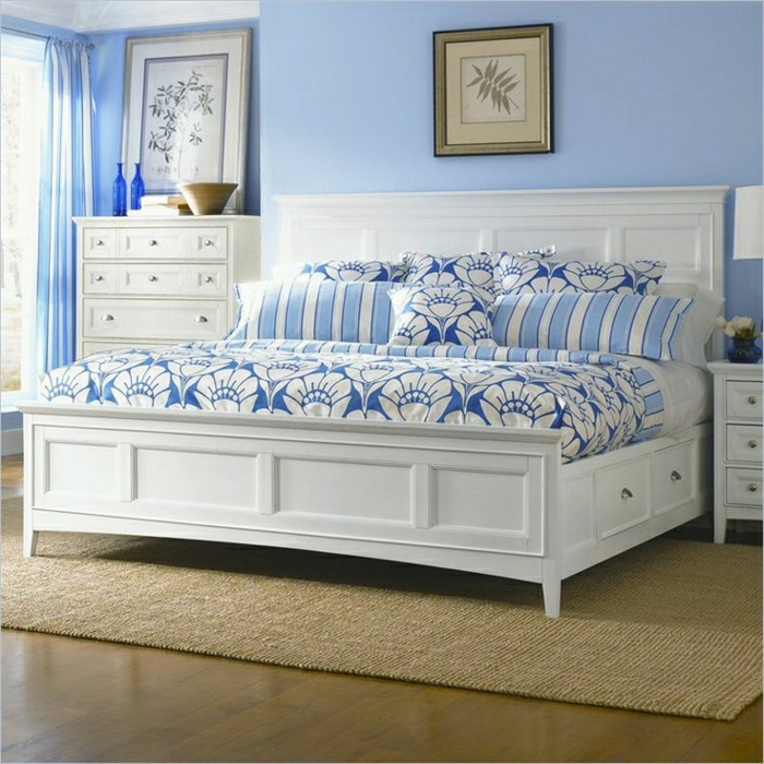 Schlafzimmer-weißes-Bett-Schubladen-blaue-Bettwäsche-Ornamente-Nachttisch-Kommode-Rattan-Teppich-blaue-Wände-Gardinen
