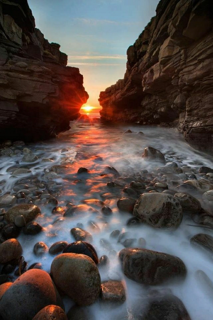 Sonnenuntergang-Felsen-Fluss-Steine