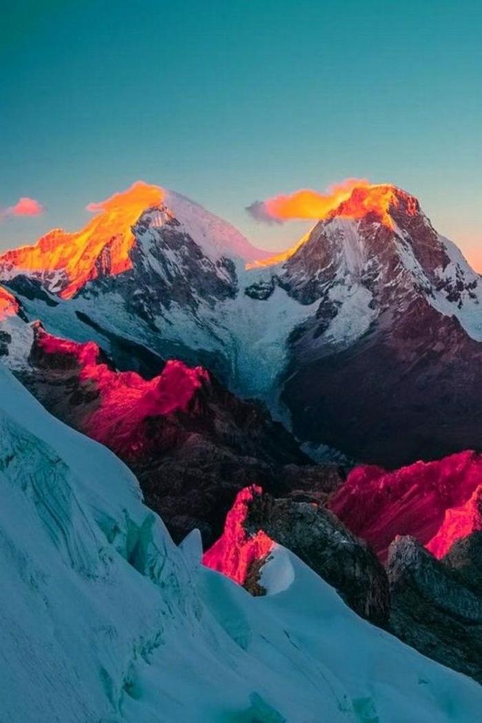 Sonnenuntergang-grelle-Nuancen-Gebirge-Schnee