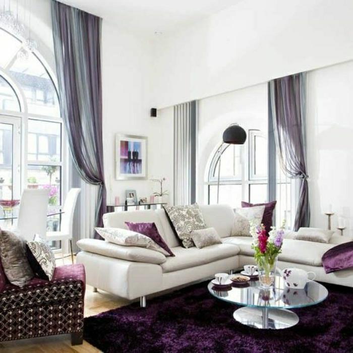 Wohnzimmer-beige-Sofa-Kissen-Teppich-Sessel-lila-Plüsch-Gardinen-Tüll-lila-blau