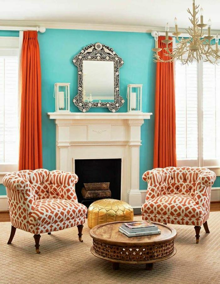 Wohnzimmer-eklektische-Gestaltung-Sessel-hölzerner-Couchtisch-Ornamente-goldener-Hocker-Kamin-blaue-Wönde-vintage-Spiegel-rustikaler-Kronleuchter-orange-Vorhänge-Rolladen