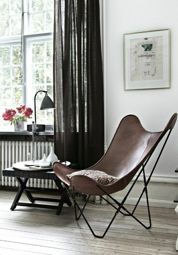Wohnzimmer-skandinavischer-Stil-Leder-Sessel-industrielle-Leselampe-rote-Blumen-Fenster-durchsichtige-Vorhänge