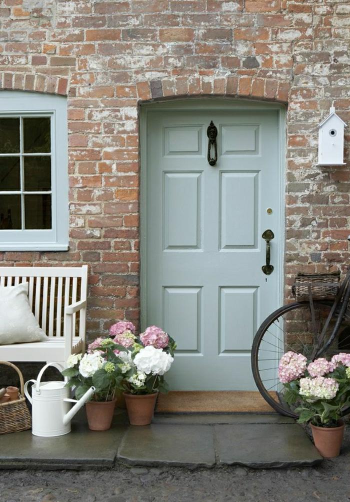 Ziegelhaus-vintage-alte-Haustüren-Fenster-weiße-Bank-Rattankorb-Blumentöpfe-Gießkanne-Fahrrad