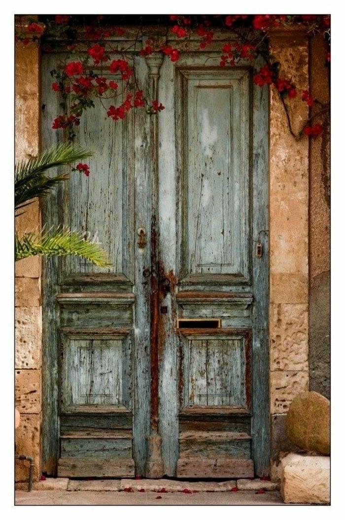 antike-Haustür-alt-vintage-retro-rote-Blumen-Steingebäude