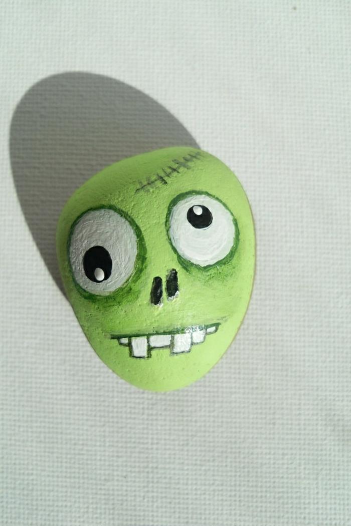 bemalter-Stein-schreckliche-Zeichnung-Zombie-Kopf-grün