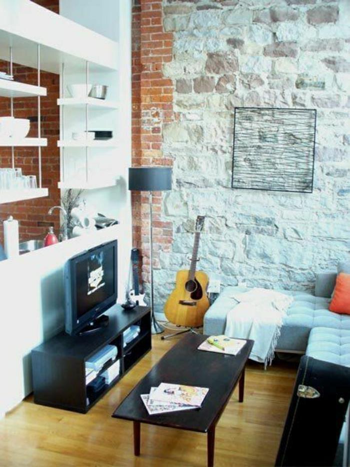das-Musikinstrument-Gitarre-Wohnzimmer-Ziegelwände-Fernseher-weiße-Regale-Sofa-Kissen-Couchtisch