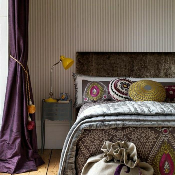 eklektische-Gestaltung-Schlafzimmer-Bett-Boho-Kissen-gelbe-Leselampe-lila-Satin-Gardinen-Quasten