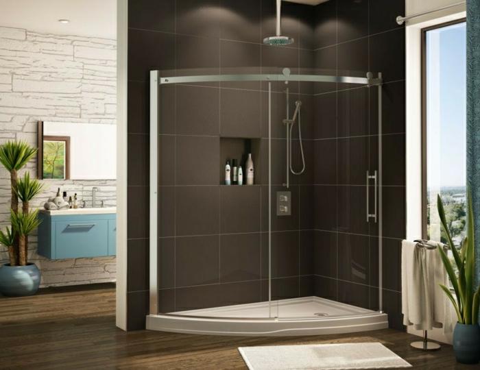 gebogene-Duschabtrennung-schwarze-Fliesen-Waschbecken-blauer-Schrank-Spiegel-Blumentopf