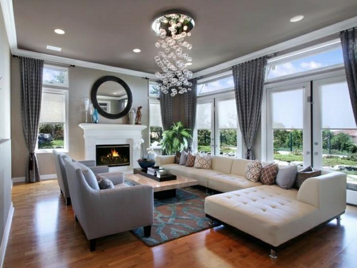 gemütliches-Wohnzimmer-Kronleuchter-Blasen-Spiegel-Sofas-beige-grau-Kamin-Pflanze-flaumiger-Teppich-Couchtisch-graue-moderne-Gardinen