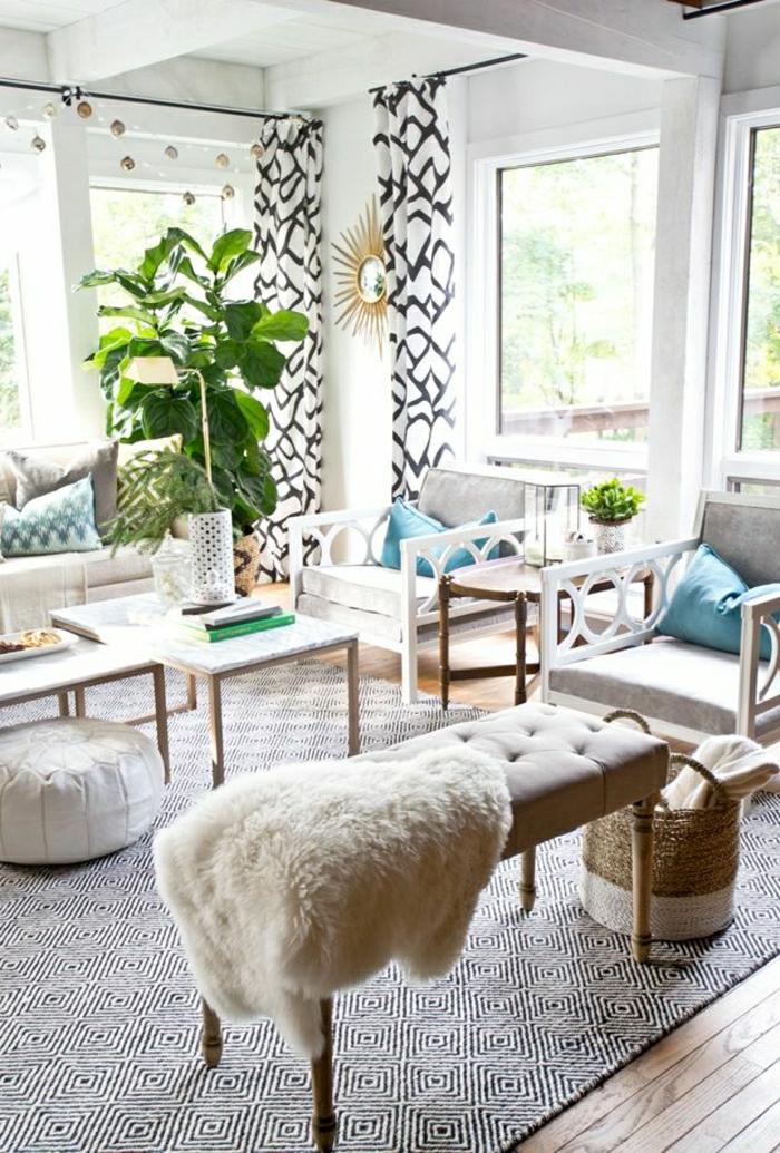 gemütliches-Wohnzimmer-graphischer-Teppich-Gardinen-goldene-Wanddekoration-Pflanzen-Tierfell-Bank